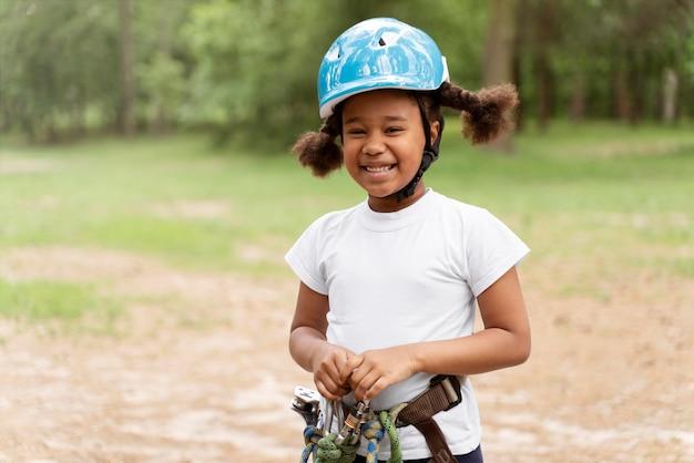 Schattig klein meisje dat plezier heeft in een avonturenpark Gratis Foto