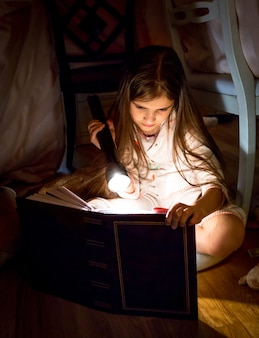 Schattig klein meisje dat 's nachts een boek leest onder deken