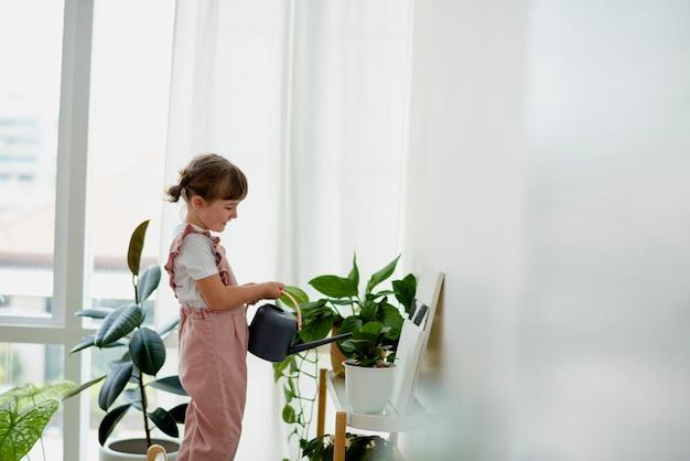 Schattig klein meisje dat thuis planten water geeft