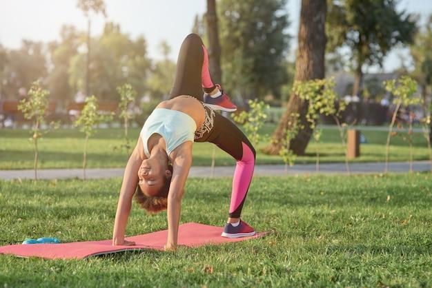 Schattig klein meisje dat yoga beoefent in het park