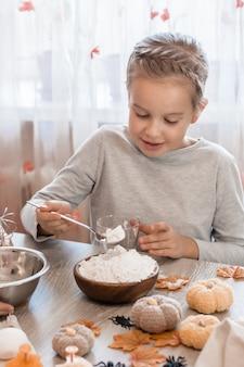 Schattig klein meisje doet bloem in een glas voor het koken van gemberdeeg voor het maken van koekjes voor halloween in de huiskeuken. traktaties en voorbereidingen voor het halloween-feest