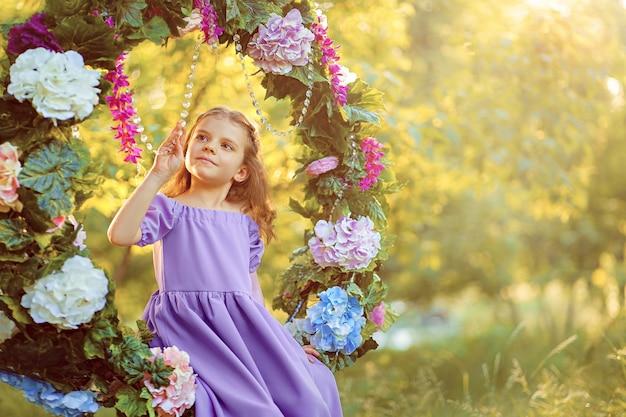 Schattig klein meisje draagt lila jurk poseren zittend in ring versierd met bloemen in het park