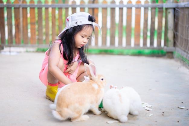 Schattig klein meisje dragen hoed voederen konijn op de boerderij