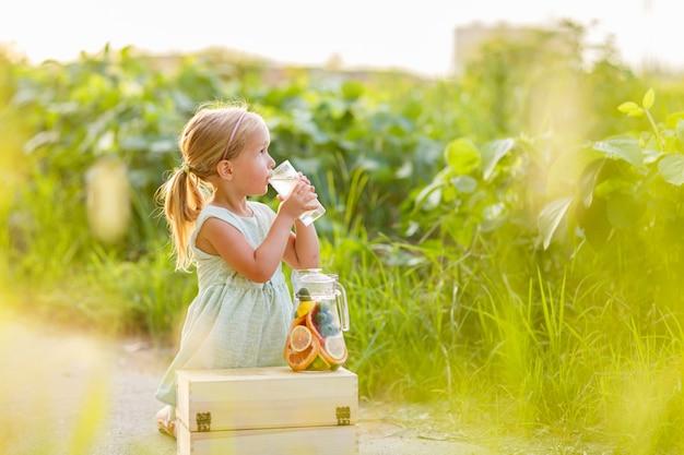 Schattig klein meisje drinkt limonade buiten.