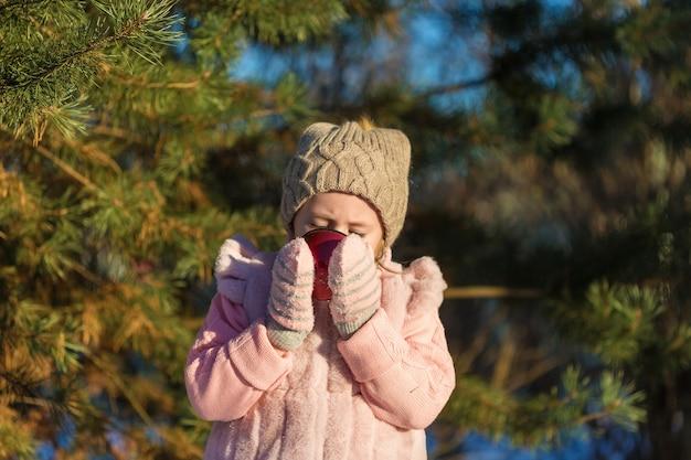 Schattig klein meisje drinkt uit een beker in winter forest. gelukkige jeugd. kids outdoors.winter fun holiday concept