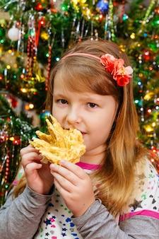 Schattig klein meisje eet cake sakotis nieuwjaar en merry christmas background