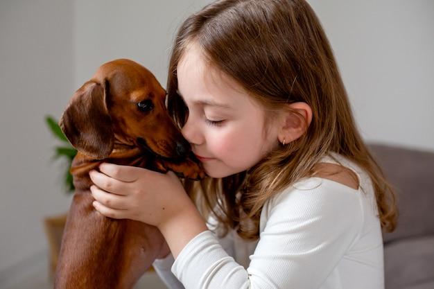 Schattig klein meisje en een dwerg teckel zitten neus aan neus op het bed en kijken elkaar aan