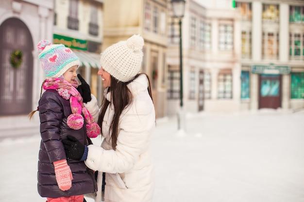 Schattig klein meisje en haar jonge moeder op een ijsbaan