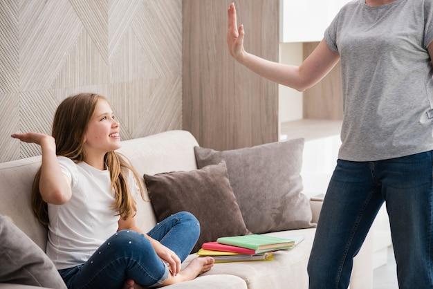 Schattig klein meisje en haar moeder geven high five terwijl ze huiswerk maken