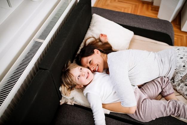 Schattig klein meisje en haar moeder in bed liggen.