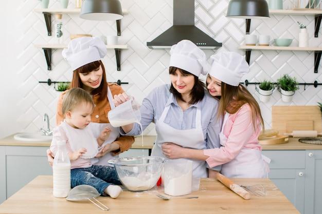 Schattig klein meisje en haar mooie moeder, tante en grootmoeder in schorten en hoeden met plezier terwijl ze melk gieten op meel en kneden van het deeg in de moderne keuken bij sweet home. vrouwen bakken in de keuken