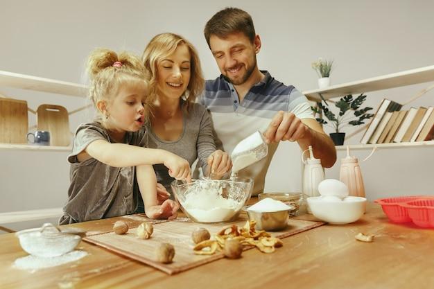 Schattig klein meisje en haar mooie ouders bereiden het deeg voor de taart in de keuken thuis