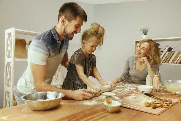 Schattig klein meisje en haar mooie ouders bereiden het deeg voor de taart in de keuken thuis.