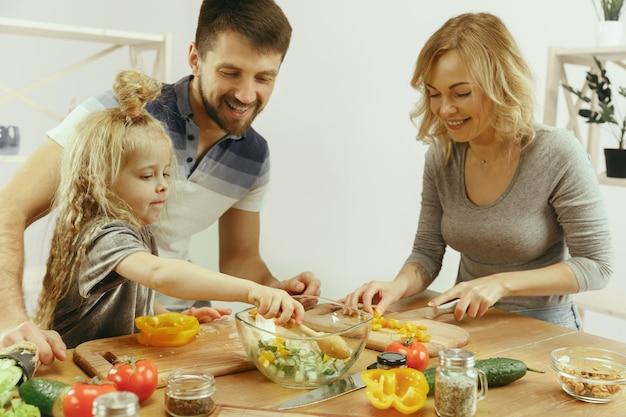 Schattig klein meisje en haar mooie ouders snijden groenten in de keuken thuis