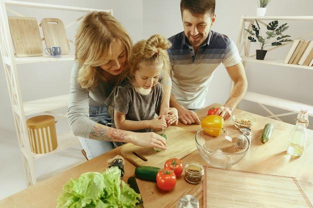 Schattig klein meisje en haar mooie ouders zijn groenten snijden en glimlachen tijdens het maken van salade in de keuken thuis. familie levensstijl concept