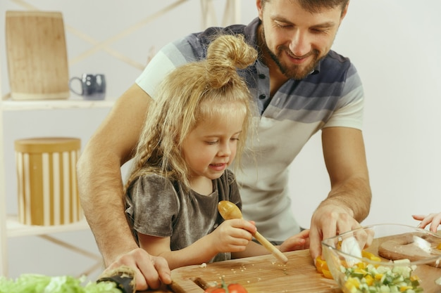 Schattig klein meisje en haar mooie ouders zijn groenten snijden en glimlachen tijdens het maken van salade in de keuken thuis