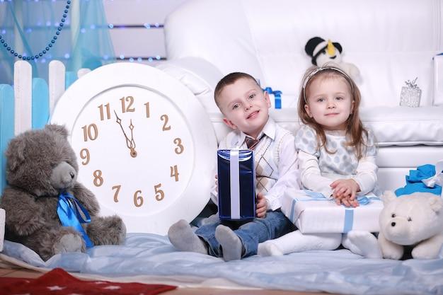 Schattig klein meisje en jongen met geschenkdozen en grote witte klok zitten in de buurt van de witte bank in kerstmis en nieuwjaar