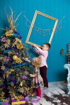 Schattig klein meisje en jongen versieren een kerstboom.