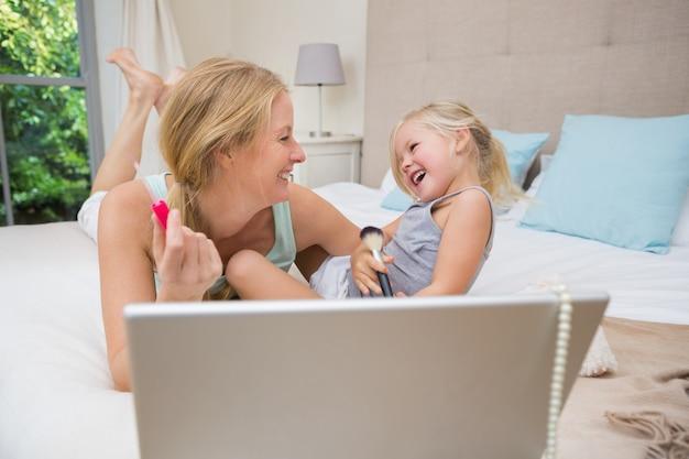 Schattig klein meisje en moeder op bed met behulp van laptop