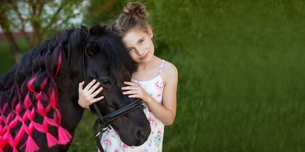 Schattig klein meisje en zwarte pony in een prachtig park. mooi meisje dat een pony omhelst. lente of zomer. kopieer ruimte voor tekst. banner