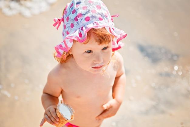 Schattig klein meisje eten van ijs op strandvakantie