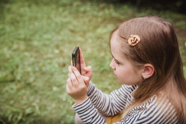 Schattig klein meisje gebruikt de slimme telefoon. gras op de achtergrond. op meisje een haarspeld met een pompoen