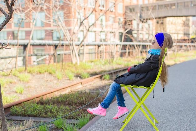 Schattig klein meisje geniet van een zonnige dag op de high line van new york