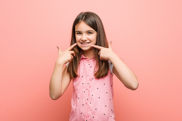 Schattig klein meisje glimlacht, wijzend op de mond.