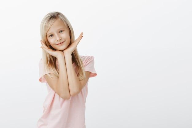 Schattig klein meisje hand in hand over het gezicht, op zoek gelukkig