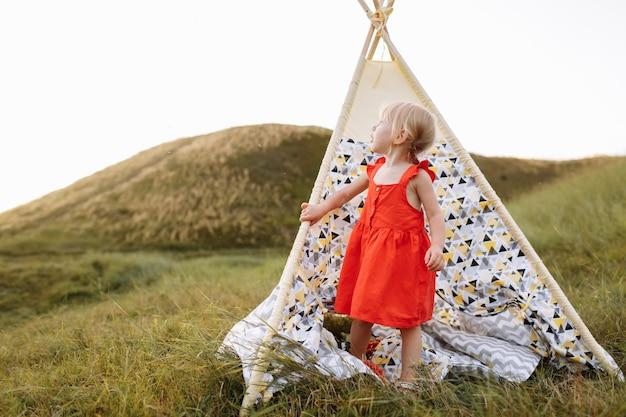 Schattig klein meisje heeft plezier in de buurt van wigwam in een zomer-veld op zonsondergang