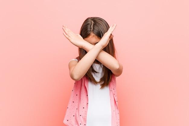 Schattig klein meisje houdt twee armen gekruist, ontkenning.