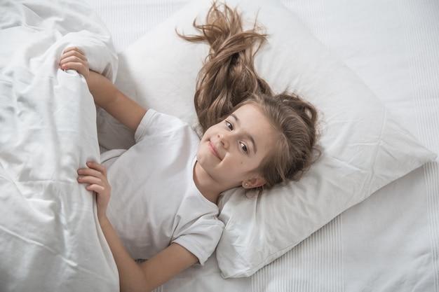 Schattig klein meisje in bed werd 's ochtends wakker