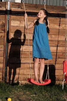 Schattig klein meisje in blauwe jurk spelen op speelplaats buiten ze swingend