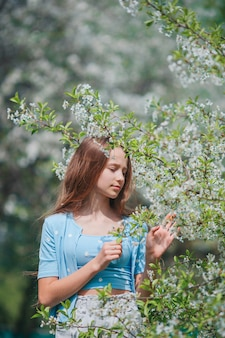 Schattig klein meisje in bloeiende appeltuin op mooie lentedag