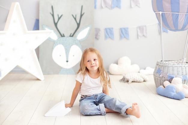 Schattig klein meisje in casual kleding speelt in de kleuterschool, houdt een papieren vliegtuigje. kinderen, plezier, games, activiteit en vrije tijd. een kind in de kinderkamer speelt. het concept van kindertijd. ballon