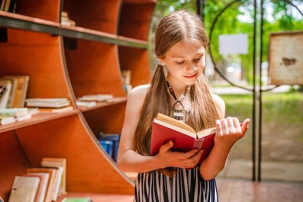 Schattig klein meisje in de bibliotheek in het park met boeken