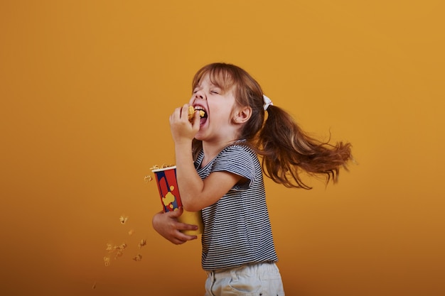 Schattig klein meisje in de studio eet popcorn en staat tegen een gele achtergrond.