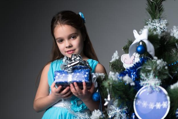 Schattig klein meisje in een blauwe jurk heeft een geschenk in haar handen in de buurt van een kerstboom op een grijze ondergrond