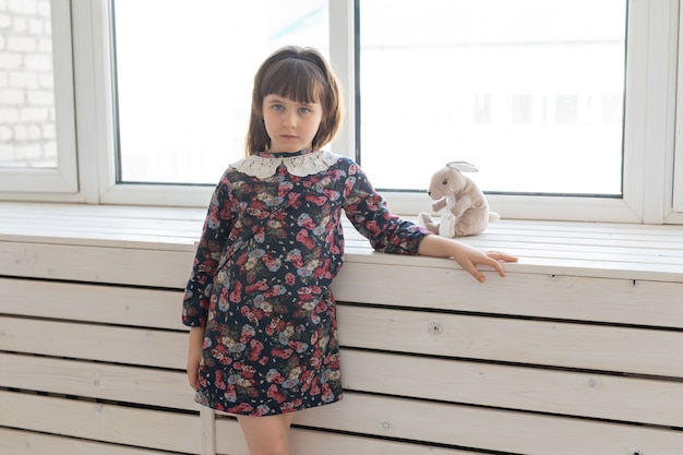 Schattig klein meisje in een bloemenjurk met een favoriet zacht speelgoedkonijntje. het concept van kinderen