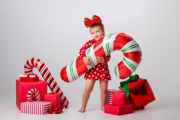 Schattig klein meisje in een feestelijk kostuum met kerstcadeaus