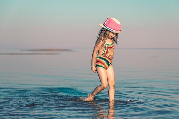 Schattig klein meisje in een gebreid zwempak en een roze hoed loopt op de zee bij de kust kopieer de ruimte