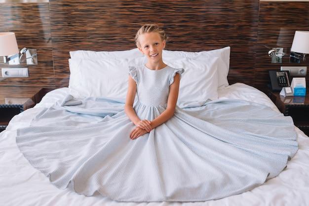 Schattig klein meisje in een geweldige jurk op het bed