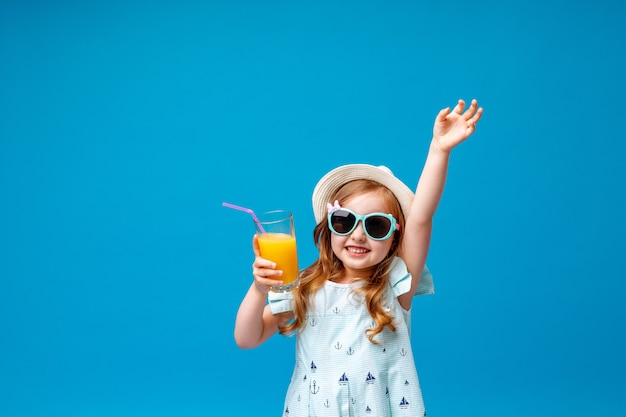 Schattig klein meisje in een jurk, hoed en zonnebril houdingen