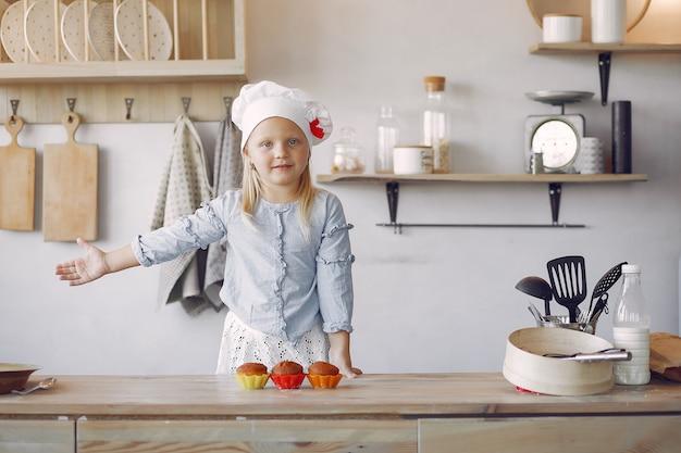 Schattig klein meisje in een keuken met cupcake