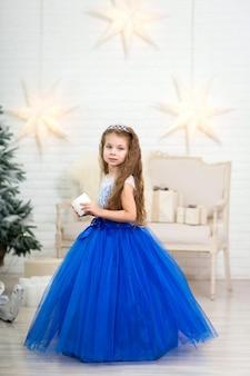 Schattig klein meisje in een prachtige blauwe jurk met een kunstmatige kaars in haar handen