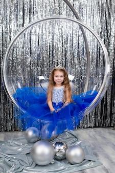 Schattig klein meisje in een prachtige blauwe jurk poseren zittend in een grote glazen bal stoel.
