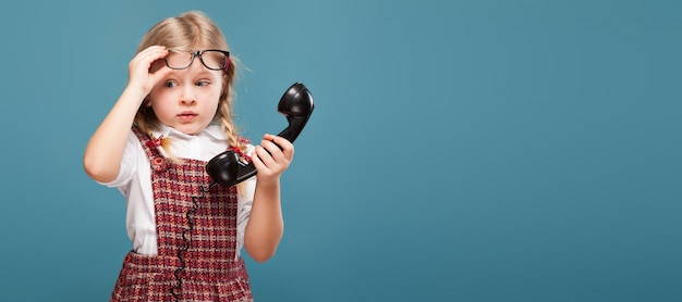 Schattig klein meisje in een rode jurk, wit shirt en bril houdt telefoonhoorn