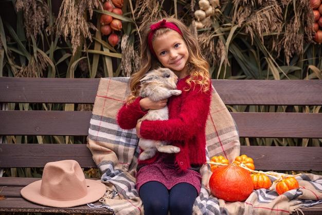 Schattig klein meisje in een rode trui houdt een konijn in haar armen herfstportret van de kinderen