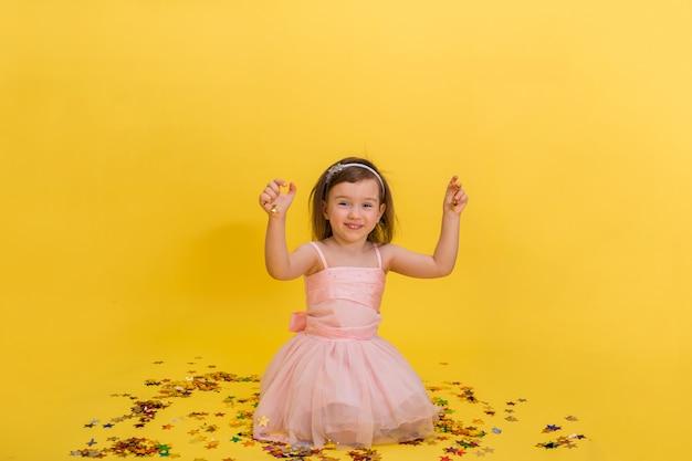 Schattig klein meisje in een roze gezwollen jurk zit en speelt met confetti. verjaardagsfeest.
