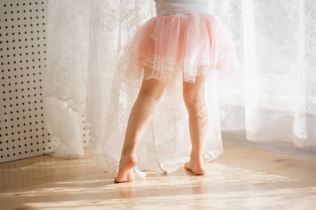Schattig klein meisje in een roze rok. prachtige zon